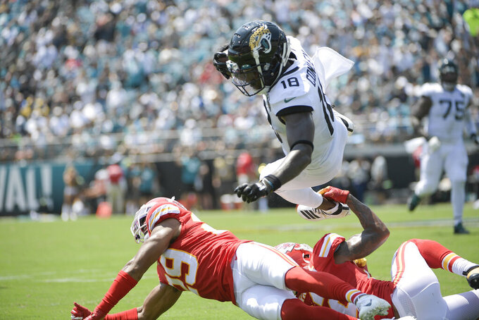 Jacksonville Jaguars wide receiver Chris Conley (18) dives over Kansas City Chiefs cornerback Kendall Fuller, lower left, after a reception during the first half of an NFL football game, Sunday, Sept. 8, 2019, in Jacksonville, Fla. (AP Photo/Phelan M. Ebenhack)