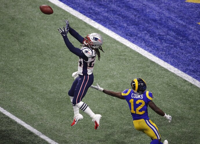New England Patriots' Stephon Gilmore (24) prepares to intercept the ball against Los Angeles Rams' Brandin Cooks (12) during the second half of the NFL Super Bowl 53 football game Sunday, Feb. 3, 2019, in Atlanta. (AP Photo/Charlie Riedel)