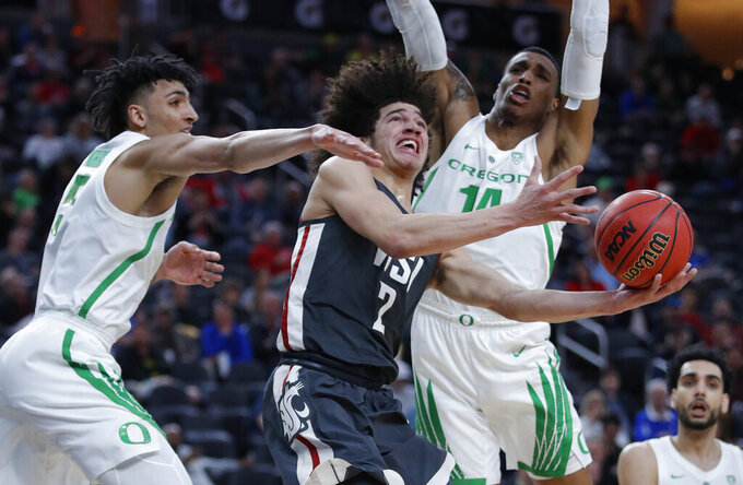 Washington State's CJ Elleby shoots between Oregon's Miles Norris, left, and Kenny Wooten during the first half of an NCAA college basketball game in the first round of the Pac-12 men's tournament Wednesday, March 13, 2019, in Las Vegas. (AP Photo/John Locher)