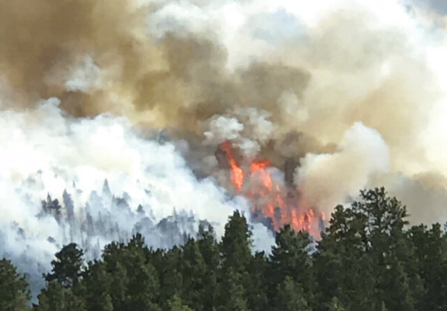 In this photo provided by Robert Brown, a wildfire burns west of Evergreen, Colo., Monday, July 13, 2020. No structures have burned, and no injuries have been reported. It's not yet clear what caused the fire. Jenny Fulton, a spokeswoman for the Jefferson County Sheriff's Office, says three evacuation orders were issued for