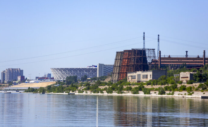 The Red October factory buildings, right, are seen next to the new the World Cup stadium, left, on the banks of the Volga River in Volgograd, Russia, Friday, June 15, 2018. Workers at the Red October steelworks in Volgograd are angry over temporary layoffs linked to the World Cup and deeper financial troubles at the factory, which sits in the shadow of the Volgograd Arena tournament venue. The situation reflects difficult daily reality in Russia even as President Vladimir Putin seeks to showcase his economic successes. (AP Photo/Dmitriy Rogulin)
