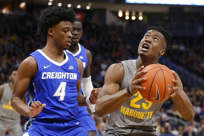 Marquette's Koby McEwen (25) looks for a shot next to Creighton's Shereef Mitchell (4) during the first half of an NCAA college basketball game Tuesday, Feb. 18, 2020, in Milwaukee. (AP Photo/Aaron Gash)