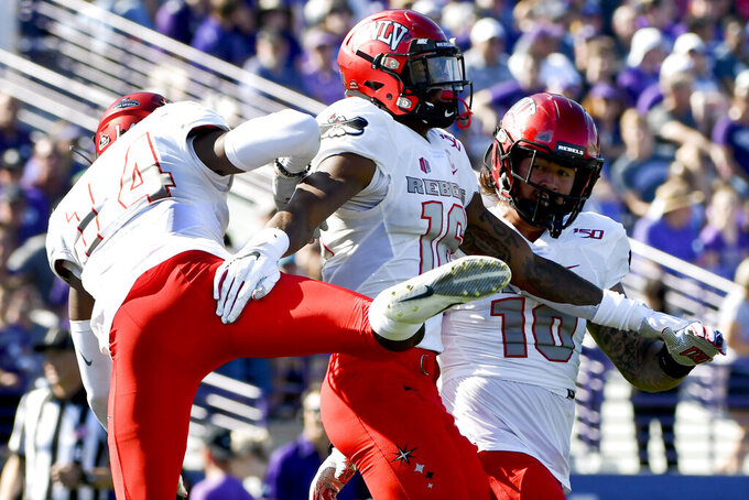 UNLV linebacker Javin White, center, celebrates with defensive back Myles Plummer (14) and linebacker Vic Viramontes (10) after he intercepted a pass against Northwestern during the first half of an NCAA college football game, Saturday, Sept. 14, 2019, in Evanston, Ill. (AP Photo/Matt Marton)