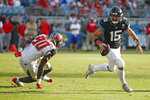 Jacksonville Jaguars quarterback Gardner Minshew (15) scrambles away from Tampa Bay Buccaneers linebacker Jason Pierre-Paul (90) during the second half of an NFL football game, Sunday Dec. 1, 2019, in Jacksonville, Fla. (AP Photo/Stephen B. Morton)
