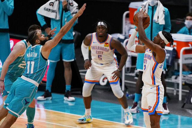Oklahoma City Thunder guard Shai Gilgeous-Alexander, right, shoots the go-ahead basket over Charlotte Hornets forward Cody Martin during the second half of an NBA basketball game in Charlotte, N.C., Saturday, Dec. 26, 2020. (AP Photo/Chris Carlson)
