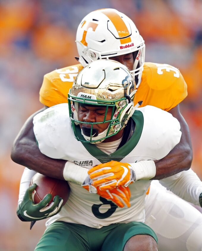 Charlotte's Nafees Lyon (8) is tackled by Tennessee linebacker Daniel Bituli (35) in the first half of an NCAA college football game Saturday, Nov. 3, 2018, in Knoxville, Tenn. (AP Photo/Wade Payne)