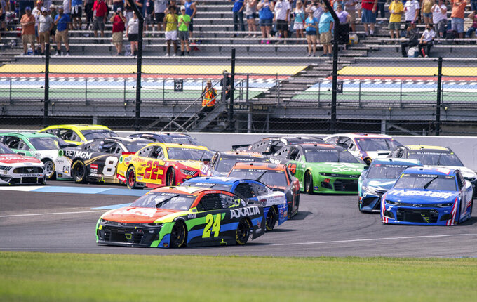 William Byron (24) leads the field of 40 cars through Turn 1 during the first lap of a NASCAR Cup Series auto race at Indianapolis Motor Speedway, Sunday, Aug. 15, 2021, in Indianapolis. (AP Photo/Doug McSchooler)