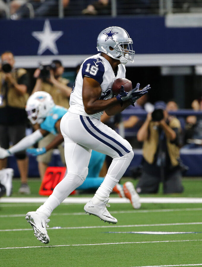 Dallas Cowboys wide receiver Amari Cooper (19) catches a pass from Dak Prescott  in the first half of an NFL football game against the Miami Dolphins in Arlington, Texas, Sunday, Sept. 22, 2019. (AP Photo/Michael Ainsworth)