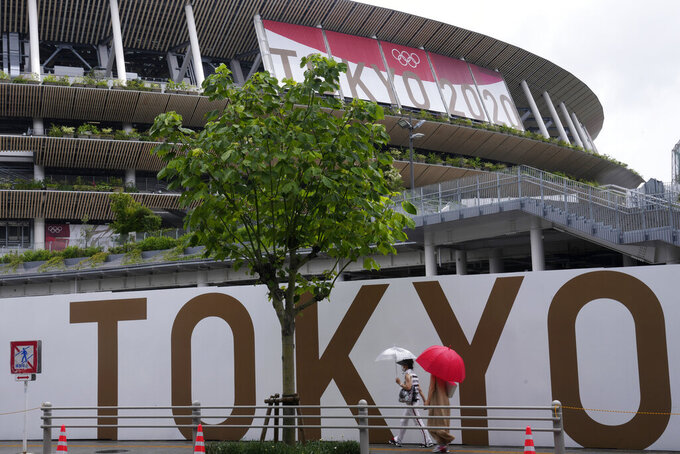 FILE - In this  July 27, 2021, file photo, people walk past the National Stadium in Tokyo. The price tag for the Tokyo Olympics is $15.4 billion. Tokyo built eight new venues. The two most expensive were the National Stadium, which cost $1.43 billion, and the new aquatic center, priced a $520 million. (AP Photo/Kiichiro Sato, File)