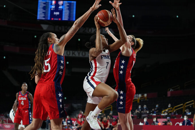 France's Sandrine Gruda (7), center, drives to the basket between United States' Brittney Griner (15), left, and Breanna Stewart (10), right, during women's basketball preliminary round game at the 2020 Summer Olympics, Monday, Aug. 2, 2021, in Saitama, Japan. (AP Photo/Eric Gay)