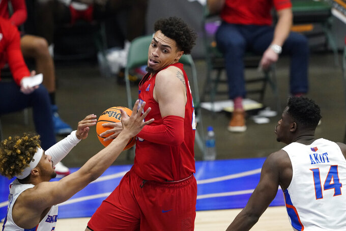 SMU forward Isiah Jasey, center, drives between Boise State guard Marcus Shaver Jr. , left, and guard Emmanuel Akot, right, during the second half of an NCAA college basketball game in the first round of the NIT, Thursday, March 18, 2021, in Frisco, Texas. (AP Photo/Tony Gutierrez)
