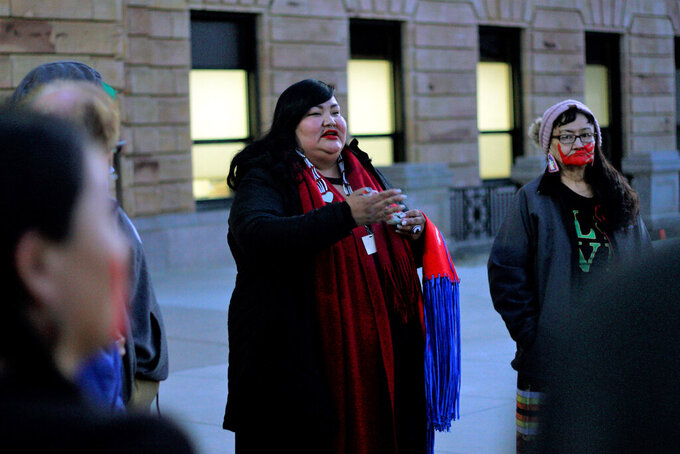 FILE - In this March 3, 2020, photo, Candi Brings Plenty, center, prays outside the Capitol in Pierre, S.D. Major construction projects moving forward along the U.S. borders with Canada and Mexico amid the coronavirus pandemic are raising fears workers could spread infections within nearby communities, including several Native American tribes. Plenty, an indigenous justice organizer with the American Civil Liberties Union, said the organization is trying to figure out creative ways to protest while still following guidelines from the Centers for Disease Control and Prevention. (AP Photo/Stephen Groves, File)