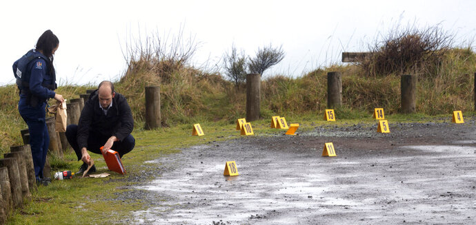 Police collect and photograph evidence in the carpark of the Te Toto Gorge lookout on Whaanga Rd, south of Raglan, New Zealand, Friday, Aug. 16, 2019. A manhunt was underway in New Zealand after an Australian tourist was killed following what police believe was a random attack on the van that he and his partner were sleeping inside. (Alan Gibson/New Zealand Herald via AP)