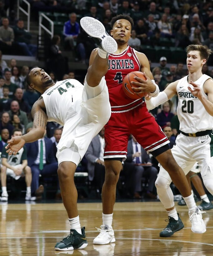 Michigan State forward Nick Ward (44) falls next to Northern Illinois forward Lacey James (4) as they fight for the rebound during the first half of an NCAA college basketball game, Saturday, Dec. 29, 2018, in East Lansing, Mich. (AP Photo/Carlos Osorio)