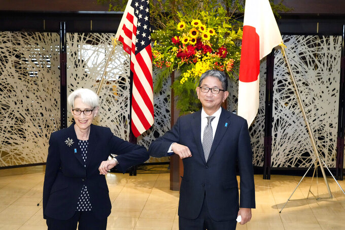 U.S. Deputy Secretary of State Wendy Sherman, left, elbow bumps with Japanese Vice-Minister for Foreign Affairs Takeo Mori, right, prior to their meeting at the Iikura Guesthouse Tuesday, July 20, 2021, in Tokyo. (AP Photo/Eugene Hoshiko, Pool)