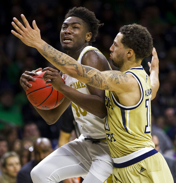 Notre Dame's Temple 'T.J.' Gibbs, left, drives in with pressure from Georgia Tech's Bubba Parham during the second half of an NCAA college basketball game Saturday, Feb. 1, 2020, in South Bend, Ind. Notre Dame won 72-80. (AP Photo/Robert Franklin)