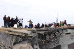 This photo provided on Jan. 30, 2020, by the Northern Democratic Brigade, a group of the US-backed Kurdish-led Syrian democratic forces, shows displaced Syrians fleeing the Syrian military offensive in Idlib province, walking over a destroyed bridge as they arrive in Manbij, north Syria. Hundreds of thousands of Syrians have fled recent government bombardment of the last rebel bastion, the northwestern Idlib province, seeking shelter from harsh winter weather in muddy tents and half-constructed buildings. As government forces advance, areas deemed safe are rapidly shrinking. (Northern Democratic Brigade, via AP)