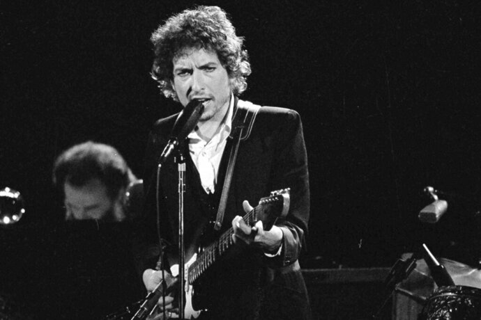 FILE - Musician Bob Dylan performs with The Band at the Forum in Los Angeles on Feb. 15, 1974. Transcripts of lost 1971 Dylan interviews with the late American blues artist Tony Glover and letters the two exchanged reveal that Dylan changed his name from Robert Zimmerman because he worried about anti-Semitism, and that he wrote