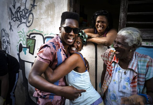 Cuban singer Cimafunk hugs a woman during the music conga through the streets of Old Havana within the activities of the 35th Havana Jazz Plaza festival in Havana, Cuba, Wednesday, Jan. 15, 2020. (AP Photo/Ramon Espinosa)