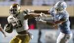 Notre Dame's Kyren Williams (23) rushes past North Carolina's Jeremiah Gemmell (44) during the fourth quarter of an NCAA college football game Friday, Nov. 27, 2020, in Chapel Hill, N.C. (Robert Willett/The News & Observer via AP, Pool)