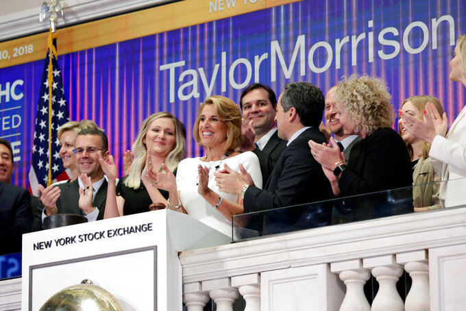 FILE -  In this April 10, 2018 file photo, Taylor Morrison Chairman, President and CEO Sheryl Palmer, in white at center, joins applause as she rings the New York Stock Exchange opening bell, to celebrate their fifth anniversary of listing. (AP Photo/Richard Drew, File)