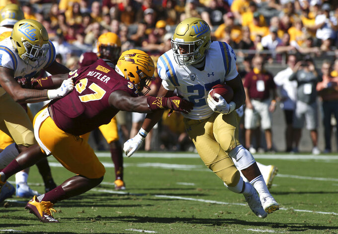 UCLA running back Joshua Kelley (27) runs the ball around Arizona State linebacker Darien Butler (37) during the first half of an NCAA college football game, Saturday, Nov. 10, 2018, in Tempe, Ariz. (AP Photo/Ralph Freso)