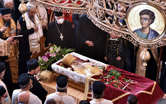 Believers pray by the coffin of Bishop Amfilohije, the head of the Serbian Orthodox Church in Montenegro, in Podgorica, Montenegro, Saturday, Oct. 31, 2020. The church said the 82-year-old died Friday from pneumonia caused by COVID-19. Amfilohije, known for his staunch anti-Western and pro-Russian political views, played a key role in leading the anti-government protests and putting together an opposition coalition that is currently trying to form the country's new government. (AP Photo/Risto Bozovic)