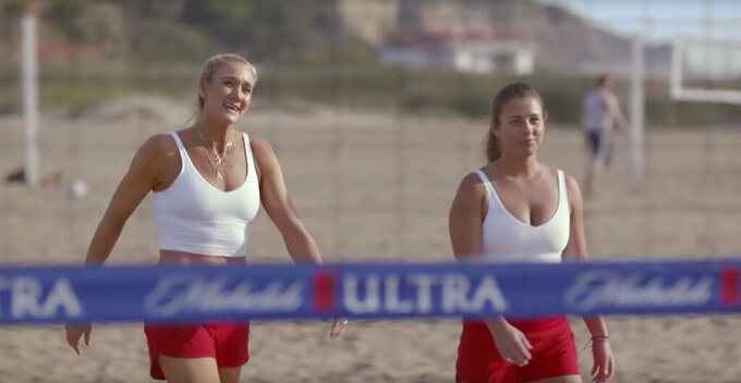 "This undated image provided by Michelob ULTRA shows Kerri Walsh Jennings, left, and Brooke Sweat in a scene from the company's 2020 Super Bowl NFL football spot. Wrestler-turned-actor John Cena tries to convince Tonight Show host Jimmy Fallon that there's a ""lighter side"" to working out, with cameos by Tonight show band The Roots and runner Usain Bolt. (Michelob ULTRA via AP)"