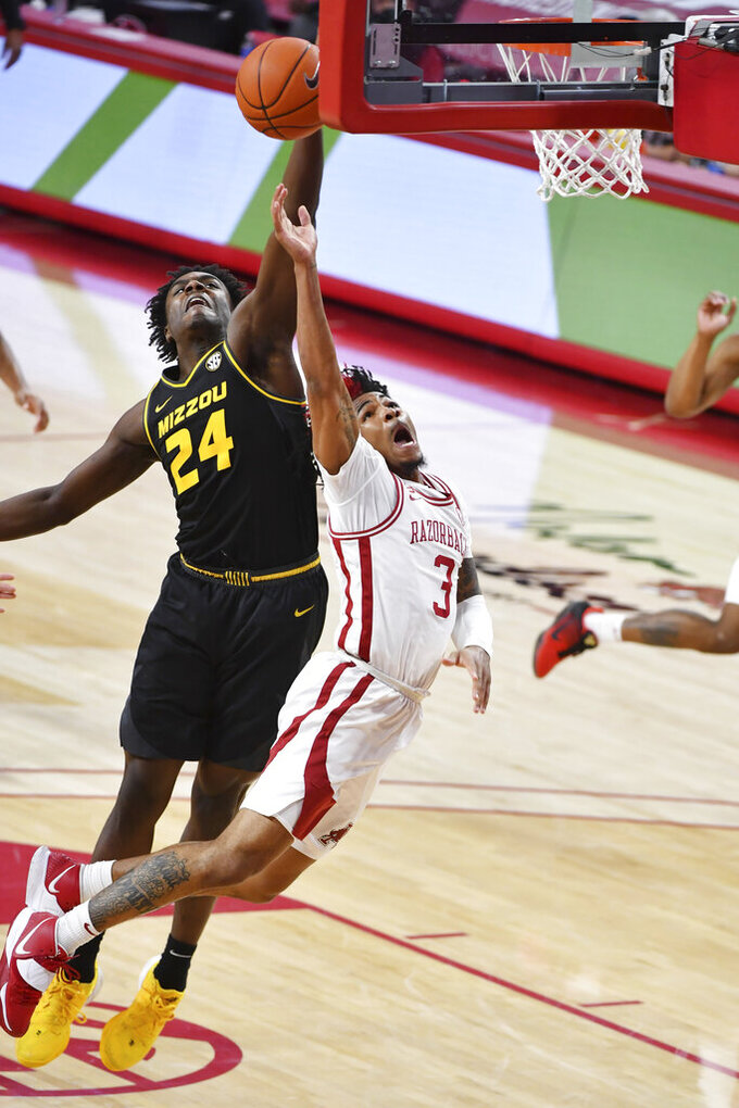 Arkansas guard Desi Sills (3) tries to drive past Missouri defender Kobe Brown (24) during the second half of an NCAA college basketball game in Fayetteville, Ark. Saturday, Jan. 2, 2021. (AP Photo/Michael Woods)