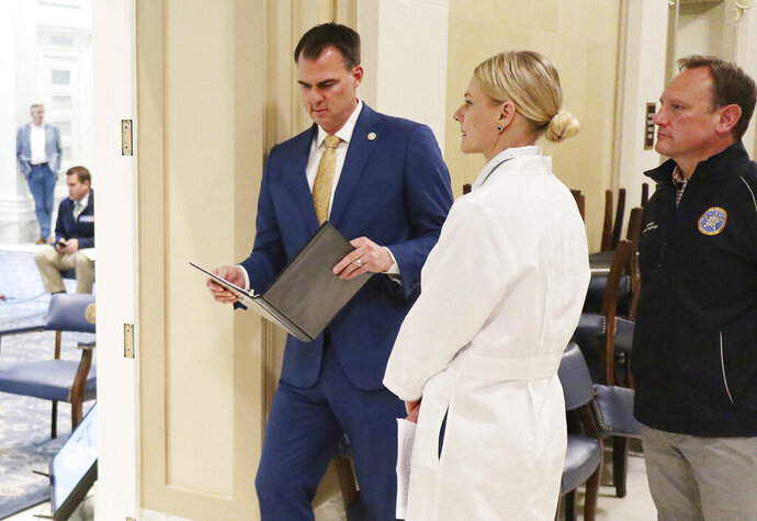 FILE - In this April 15, 2020, file photo, Oklahoma Gov. Kevin Stitt, left, Kayse Shrum, center, and Jerome Loughridge, right, wait before a media briefing in Oklahoma City for the Governor's Solution Task Force to provide an update on Oklahoma's COVID-19 response. Stitt's office announced in a press release Monday, June 29, that Loughridge - the secretary of Health and Mental Health - and Shrum, the secretary of Science and Innovation, are resigning. The two had been working as volunteers in Stitt's cabinet. (Doug Hoke/The Oklahoman via AP, File)