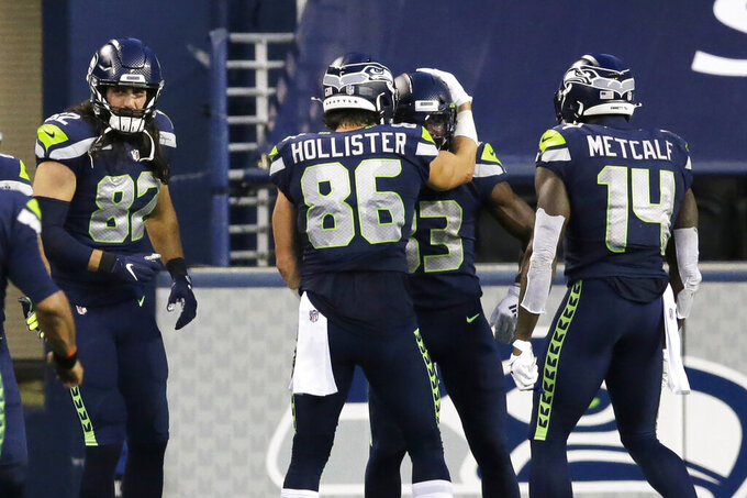 Seattle Seahawks wide receiver David Moore, second from right, is greeted by teammates after he caught a pass for a touchdown against the New England Patriots during the second half of an NFL football game, Sunday, Sept. 20, 2020, in Seattle. (AP Photo/John Froschauer)