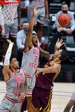Ohio State guard Musa Jallow (2) goes up to block the shot of Minnesota guard Tre' Williams (1) in the first half of an NCAA college basketball game at the Big Ten Conference tournament in Indianapolis, Thursday, March 11, 2021. (AP Photo/Michael Conroy)