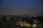 A lunar eclipse occurs over Santiago, Chile, early Wednesday, May 26, 2021. (AP Photo/Esteban Felix)