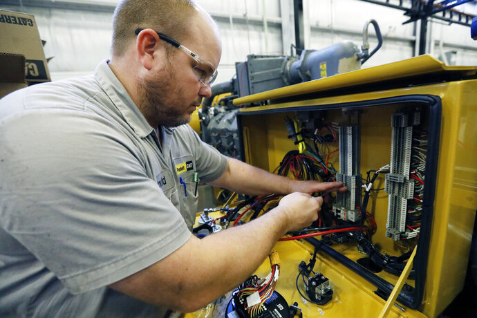 In this Sept. 18, 2019, photo technician David Boxx works on updating an electrical system on a Caterpillar machine at the Puckett Machinery Company in Flowood, Miss. On Thursday, Oct. 17, the Federal Reserve reports on U.S. industrial production for September. (AP Photo/Rogelio V. Solis)
