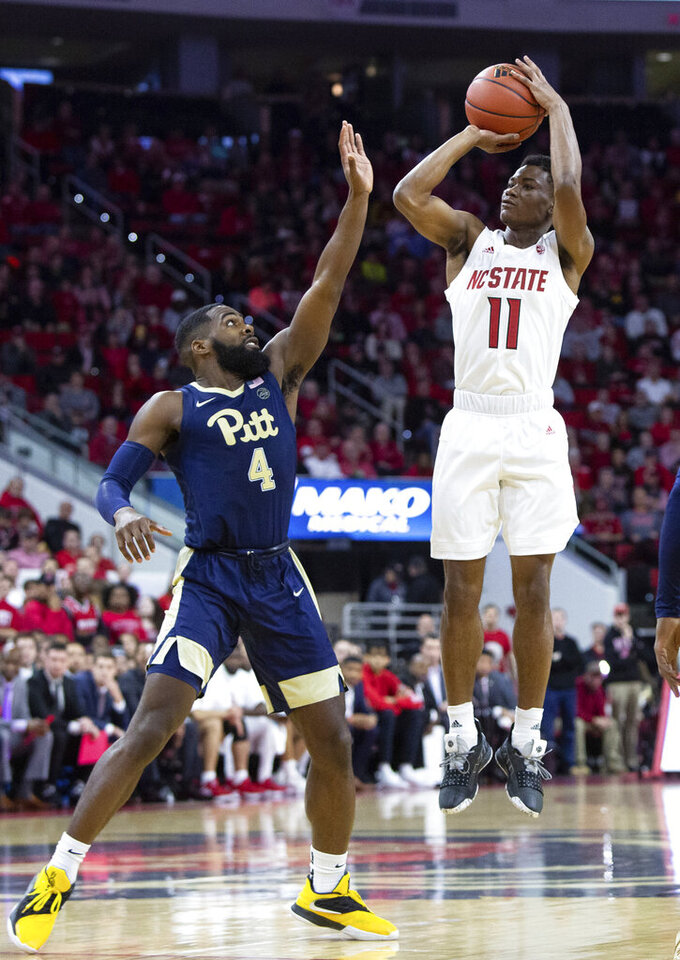 North Carolina State's Markell Johnson (11) attempts a shot over Pittsburgh's Jared Wilson-Frame (4) during the first half of an NCAA college basketball game in Raleigh, N.C., Saturday, Jan. 12, 2019. (AP Photo/Ben McKeown)