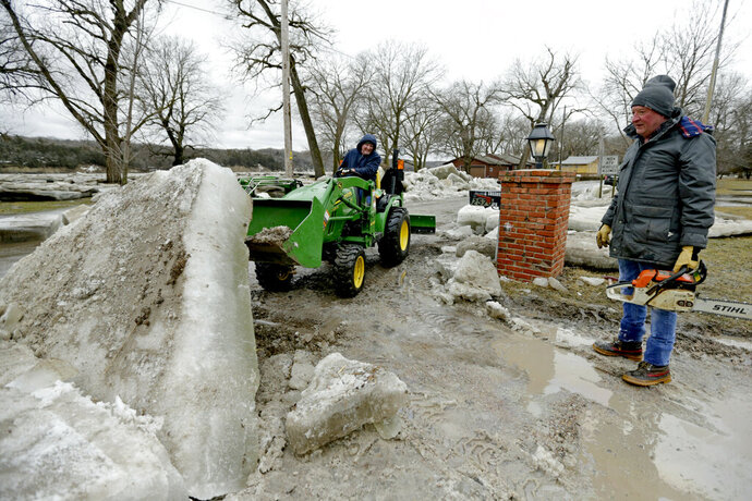 Jim Freeman, right, and his son Chad, work to clear thick ice slabs from his property in Fremont, Neb., Thursday, March 14, 2019, after the ice-covered Platte River flooded it's banks. Evacuations forced by flooding have occurred in several eastern Nebraska communities. (AP Photo/Nati Harnik)