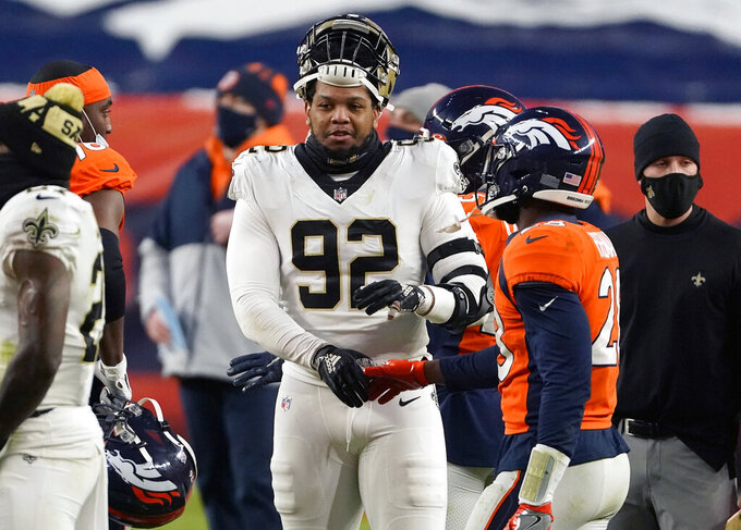 FILE - In this Sunday, Nov. 29, 2020 file photo, New Orleans Saints defensive end Marcus Davenport (92) greets Denver Broncos running back Royce Freeman after an NFL football game in Denver. New Orleans Saints general manager Mickey Loomis says the club has exercised the fifth-year option on defensive end and 2018 first-round draft choice Marcus Davenport. (AP Photo/Jack Dempsey, File)