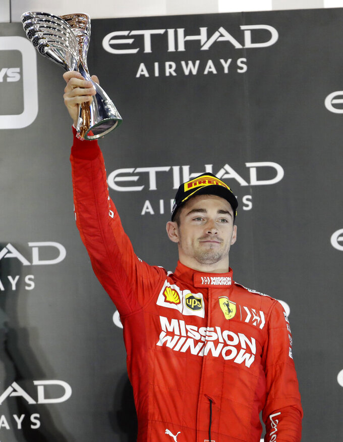 Ferrari driver Charles Leclerc of Monaco holds the trophy on the podium after he placed third in the Emirates Formula One Grand Prix, at the Yas Marina racetrack in Abu Dhabi, United Arab Emirates, Sunday, Dec.1, 2019. (AP Photo/Luca Bruno)