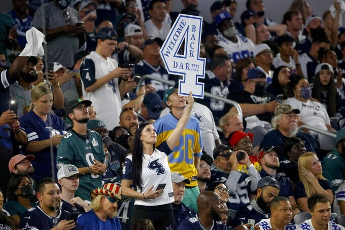 A fan holds up a sign that makes reference to Dallas Cowboys quarterback Dak Prescott (4) in the first half of an NFL football game against the Philadelphia Eagles in Arlington, Texas, Monday, Sept. 27, 2021. (AP Photo/Michael Ainsworth)