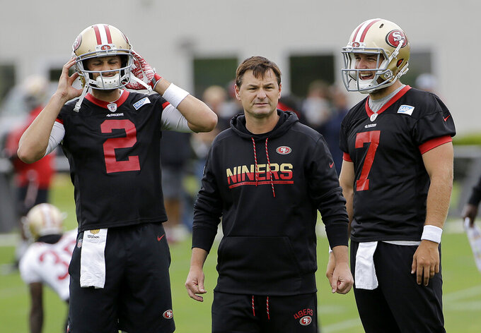 FILE - In this June 8, 2017, file photo, San Francisco 49ers quarterbacks coach Rich Scangarello, center, watches practice between Brian Hoyer, left, and Matt Barkley during the team's organized team activity at its NFL football training facility in Santa Clara, Calif. Scangarello was hired Wednesday, Jan. 16, 2019, by the Denver Broncos as offensive coordinator. (AP Photo/Jeff Chiu, File)