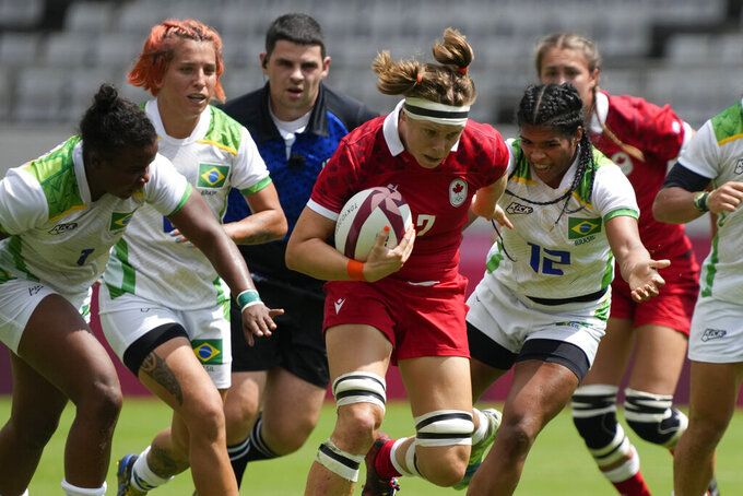 Canada's Karen Paquin, center, is pursued by Brazil's, from left, Mariana Nicolau, Luiza Campos, and Thalita da Silva Costa, as she runs on her way to scoring a try, in their women's rugby sevens match at the 2020 Summer Olympics, Thursday, July 29, 2021 in Tokyo, Japan. (AP Photo/Shuji Kajiyama)