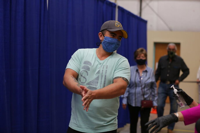 Democratic primary voter Sergio Marquez, 34, spreads sanitizing gel on his hands as he reenters a polling place to vote for congressional candidate Joseph Salazar in the primary, Tuesday, June 2, 2020, in Santa Fe, New Mexico. Marquez said an absentee ballot he requested never came and that a server issue at the polling place delayed him from voting in person. The problem was resolved within an hour and he was able to vote. (AP Photo/Cedar Attanasio)