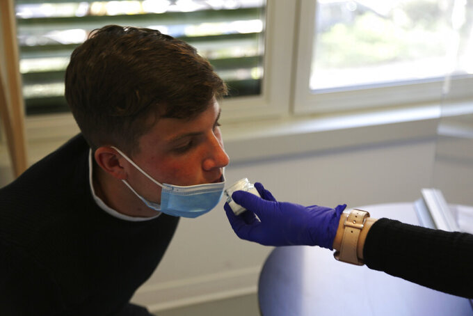 Evan Cesa, a patient, smells a small pot of fragrance during tests in a clinic in Nice, France, on Monday, Feb. 8, 2021, to help determine how his sense of smell and taste have been degraded since he contracted COVID-19 in September 2020. A year into the coronavirus pandemic, doctors are striving to better understand and treat patients who lose their sense of smell. (AP Photo/John Leicester)