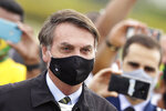 FILE - In this May 25, 2020, file photo, Brazil's President Jair Bolsonaro, wearing a face mask amid the coronavirus pandemic, stands among supporters as he leaves his official residence of Alvorada palace in Brasilia, Brazil. Bolsonaro said Tuesday, July 7, he tested positive for COVID-19 after months of downplaying the virus's severity while deaths mounted rapidly inside the country. (AP Photo/Eraldo Peres, File)