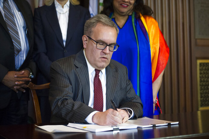 Acting EPA Administrator Andrew Wheeler signs an order withdrawing an Obama era emissions standards policy, at the EPA Headquarters in Washington, Thursday, Dec. 6, 2018. (AP Photo/Cliff Owen)