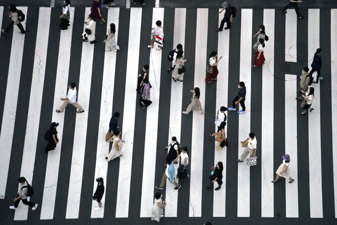 People wearing protective masks to help curb the spread of the coronavirus walk along a pedestrian crossing Thursday, July 22, 2021, in Tokyo. The Japanese capital confirmed more than 1900 new coronavirus cases on Thursday. (AP Photo/Eugene Hoshiko)
