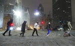 A group of people cross North Michigan Avenue during a snowstorm Friday, Jan. 17, 2020, in Chicago.  A winter storm that has already caused trouble at airports in Chicago and Kansas City was expected to bring blizzard conditions to the Plains and Midwest on Saturday and could dump up to a foot of snow in parts of the Northeast on Sunday. (John J. Kim /Chicago Tribune via AP)