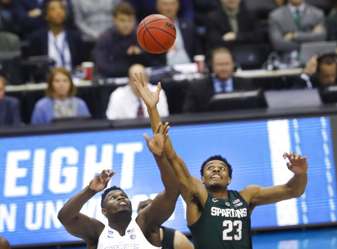 Duke forward Zion Williamson (1) and Michigan State forward Xavier Tillman (23) jump for control of the ball during the opening tip off during the first half of an NCAA men's East Regional final college basketball game in Washington, Sunday, March 31, 2019. (AP Photo}