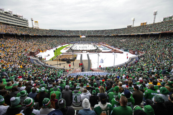 FILE - In this Jan. 1, 2020, file photo, fans watch the NHL Winter Classic hockey game between the Dallas Stars and the Nashville Predators at the Cotton Bowl in Dallas. Outdoor games have become the the marquee event of the NHL season ever since the league staged the first Winter Classic in Buffalo in 2008. None of the 30 previous outdoor games had quite a setup like this season when the league will stage two games this weekend on the 18th fairway of a golf course on the shores of Lake Tahoe, with the Sierra Nevada Mountains towering in the background. (AP Photo/Jeffrey McWhorter, File)
