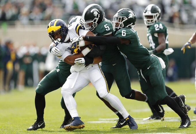 Michigan running back Chris Evans is tackled by Michigan State linebacker Andrew Dowell (5) and safety David Dowell (6) during the first half of an NCAA college football game, Saturday, Oct. 20, 2018, in East Lansing, Mich. (AP Photo/Carlos Osorio)